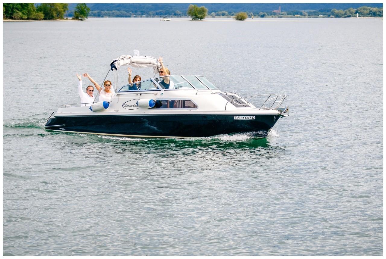 Hochzeit auf dem Chiemsee, das Brautpaar fährt mit einem Boot zur Trauung