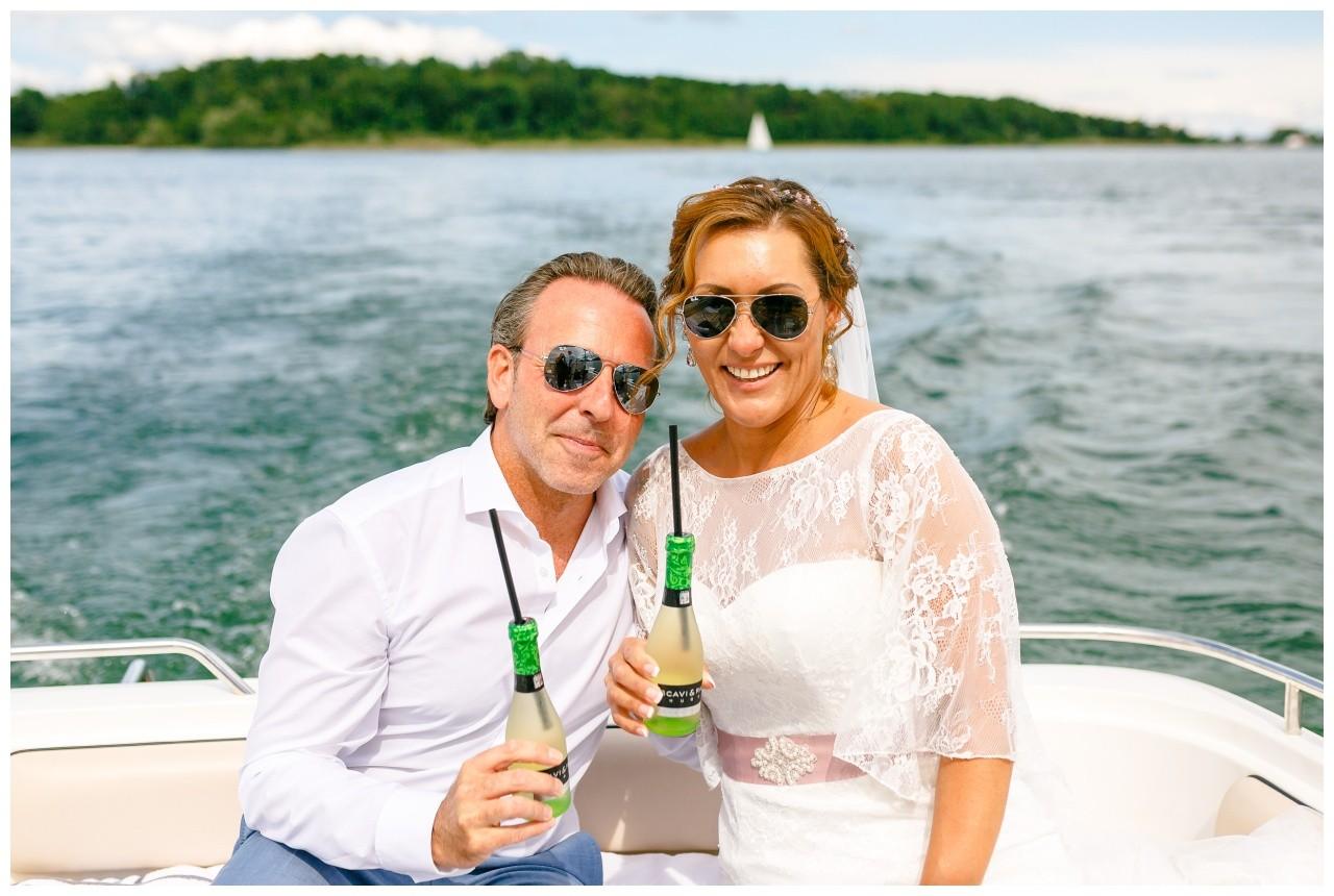 Das Brautpaar sitzt auf einem Bott und trinkt Prosecco auf dem Chiemsee
