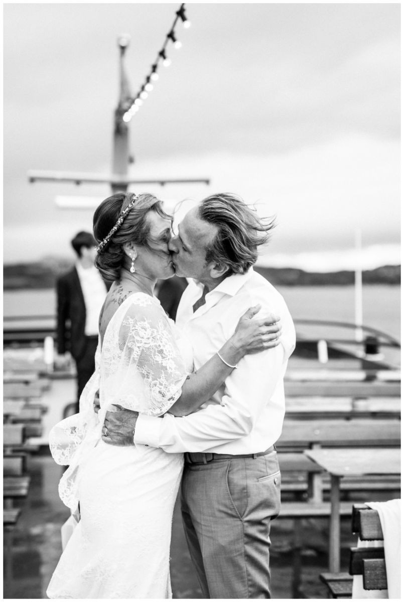 Das Brautpaar küsst sich auf dem Schiff auf dem Chiemsee