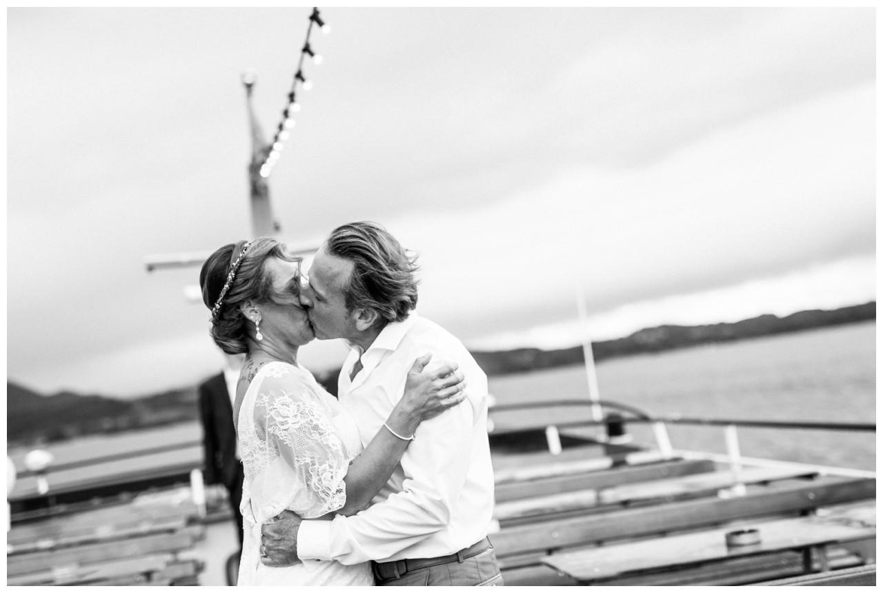Das Brautpaat küsst sich auf dem Schiff auf dem Chiemsee
