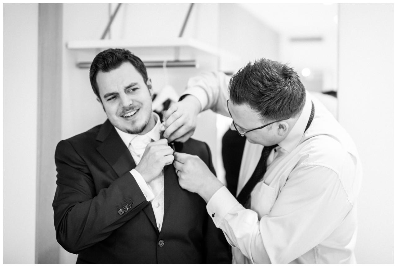 Getting Ready vorv der Hochzeit im Ruhrpott der Trauzeuge hilft dem Bräutigam beim Ankleiden
