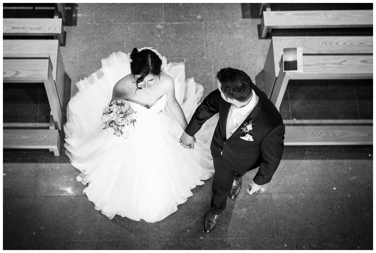 Hochzeitsfotograf Gelsenkirchen das Brautpaar geht Hand in Hand aus der Kirche bei der Hochzeit im Pott