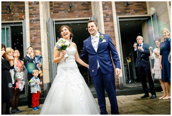 Das Brautpaar steht vor der Kirche und wird lachend von den Gästen vor der Kirche in Gelsenkirchen empfangen.