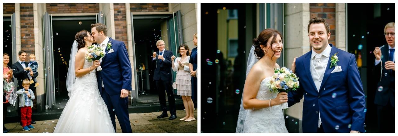 Das Brautpaar kommt bei der Hochzeit in Gelsenkirchen aus der Kirche heraus und wird von den Hochzeitsgästen mit Seifenblasen empfangen