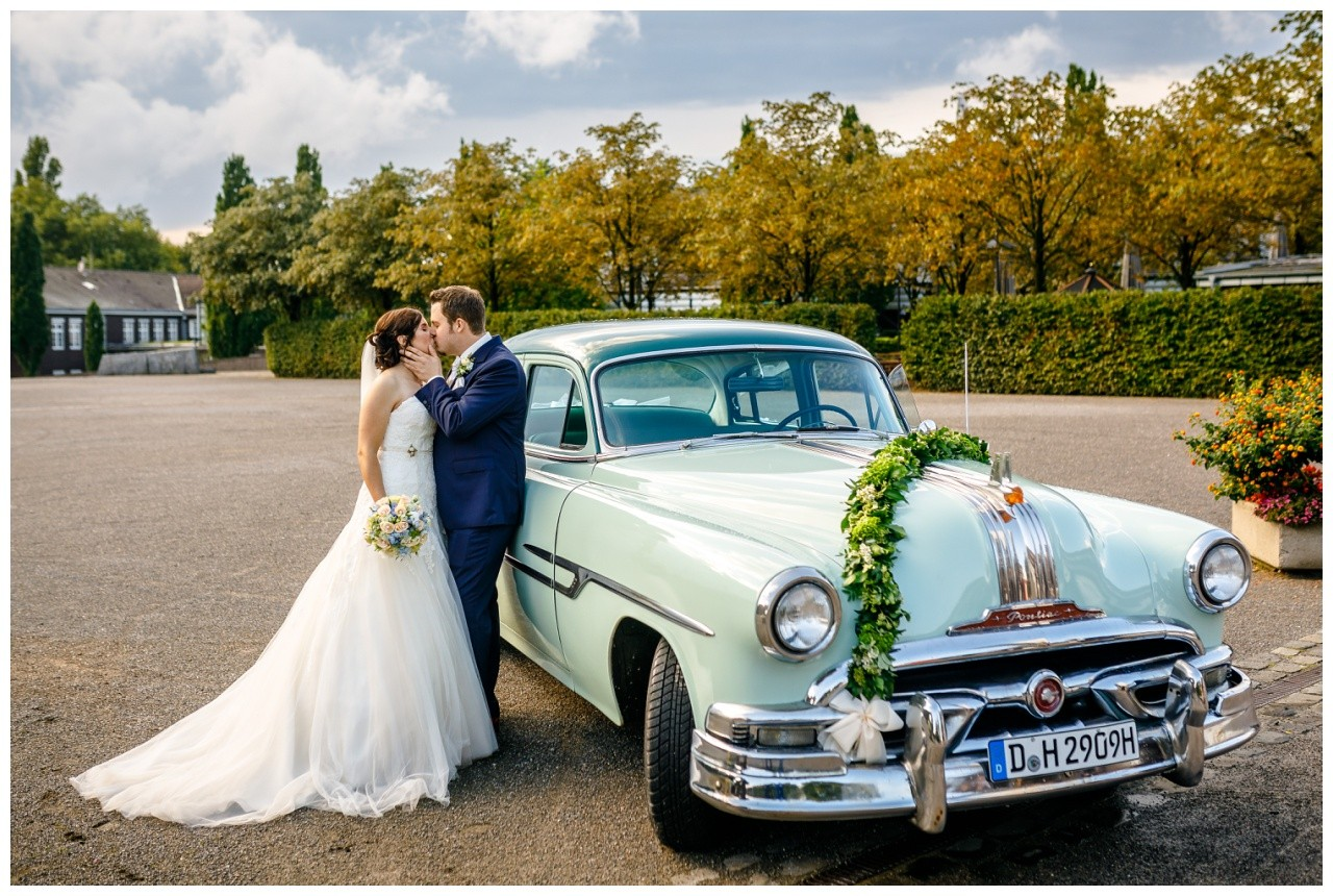 Das Brautpaar in Gelsenkirchen steht vor dem Brautauto im Ruhrgebiet