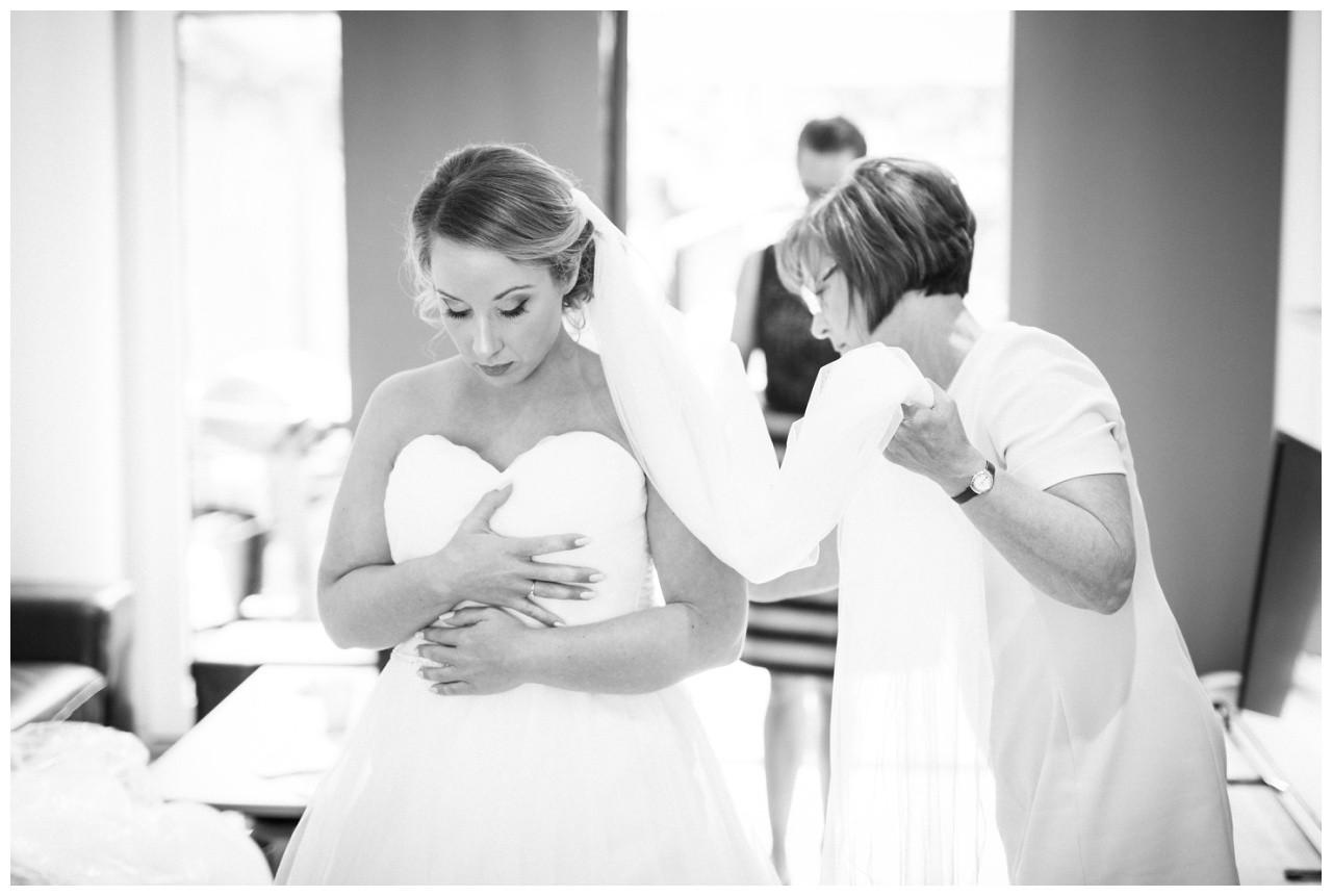 Die Brautmutter hilft der Braut ins Brautkleid vor der Hochzeit in Mönchengladbach