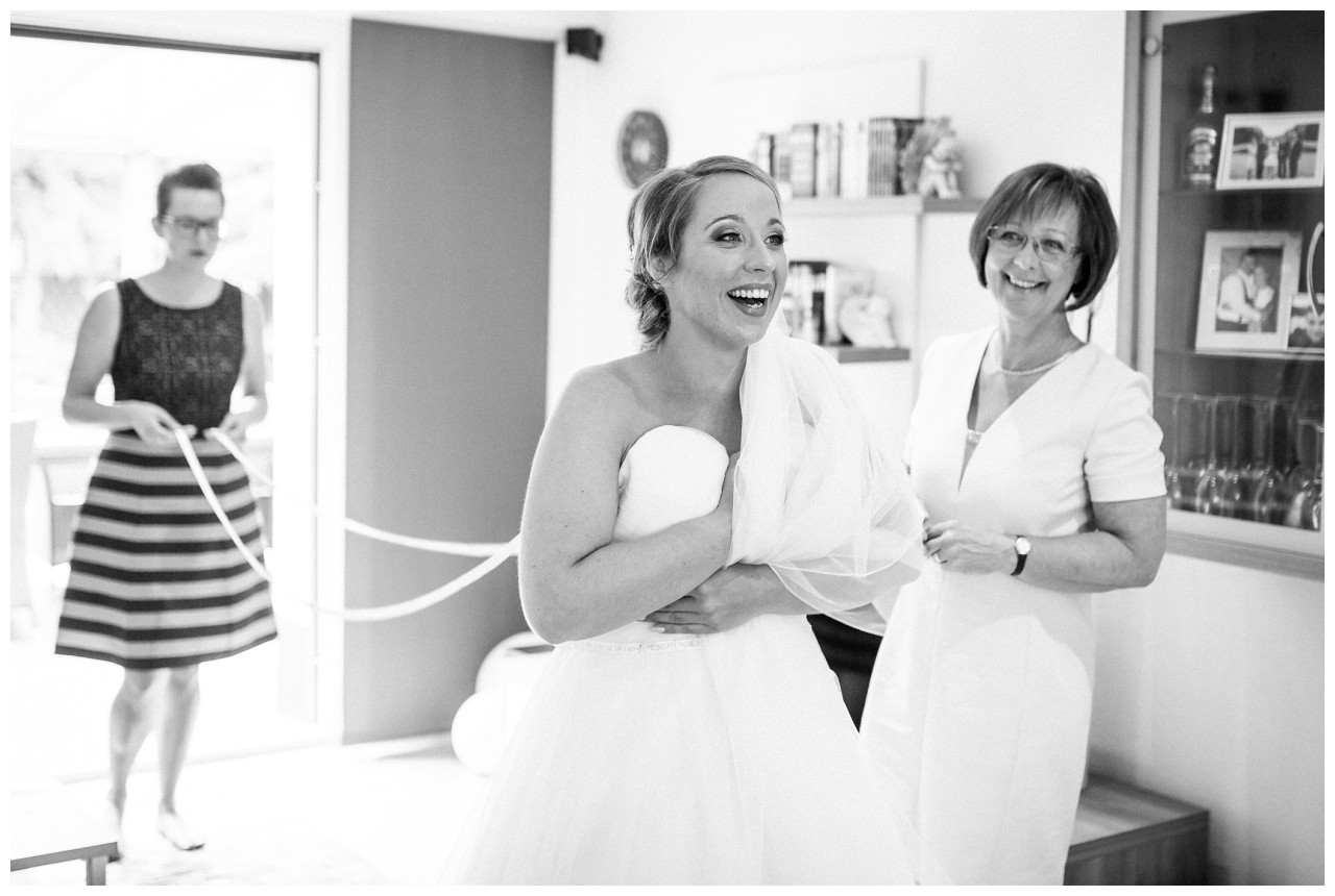 Die Braut lacht herzlich als sie ins Brautkleid geschnürt wird vor der Hochzeit in Mönchengladbach