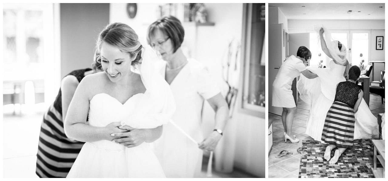 Brautmutter und Trauzeugin helfen der Braut beim Anziehen des Brautkleids in Mönchengladbach
