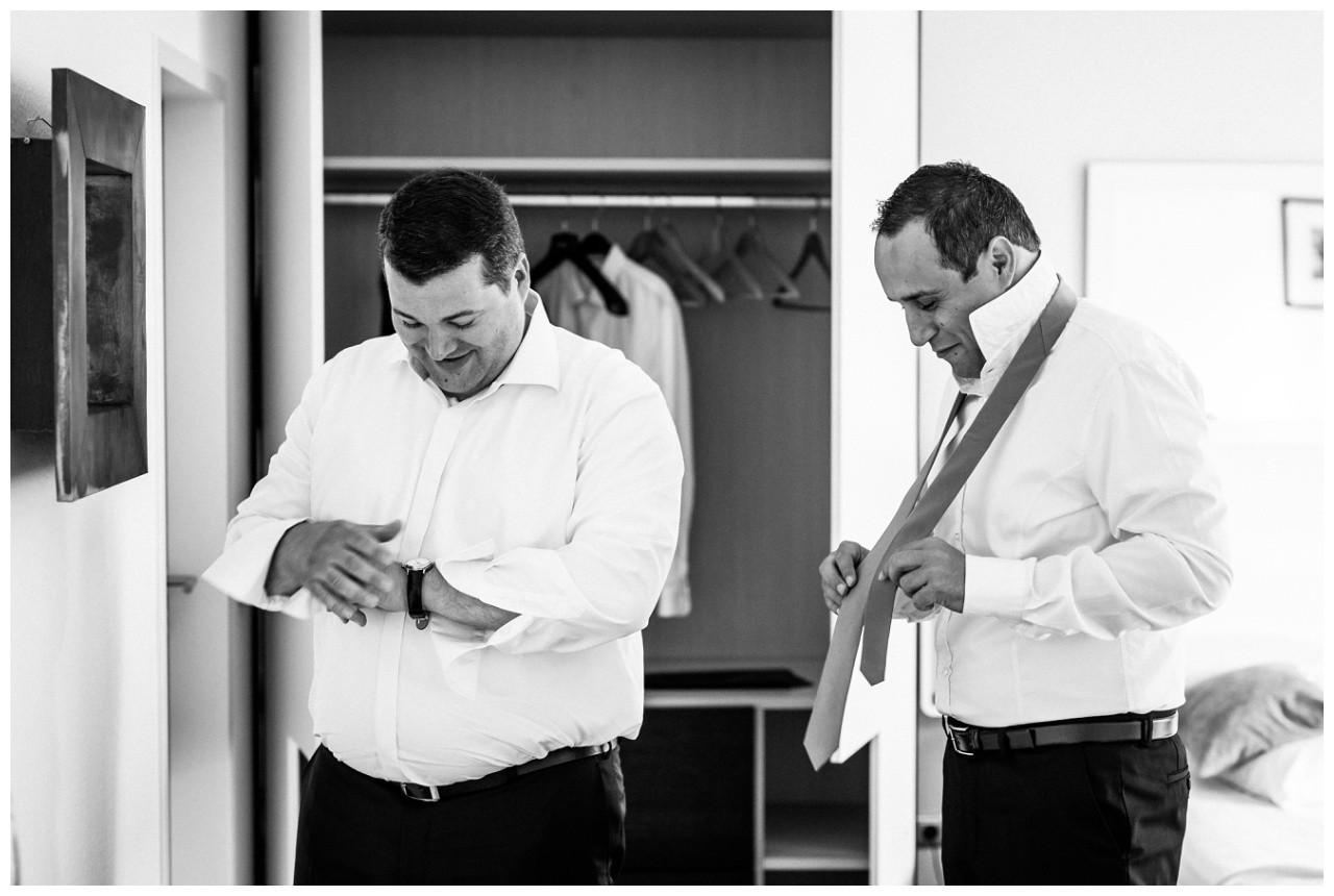 Bräutigam und Trauzeuge ziehen sich an vor der Hochzeit in Krefeld
