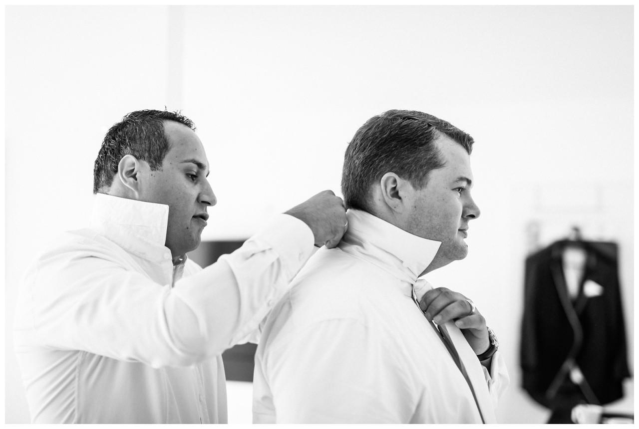 Der Trauzeuge bindet dem Bräutigam die Krawatte vor der Hochzeit in Mönchengladbach