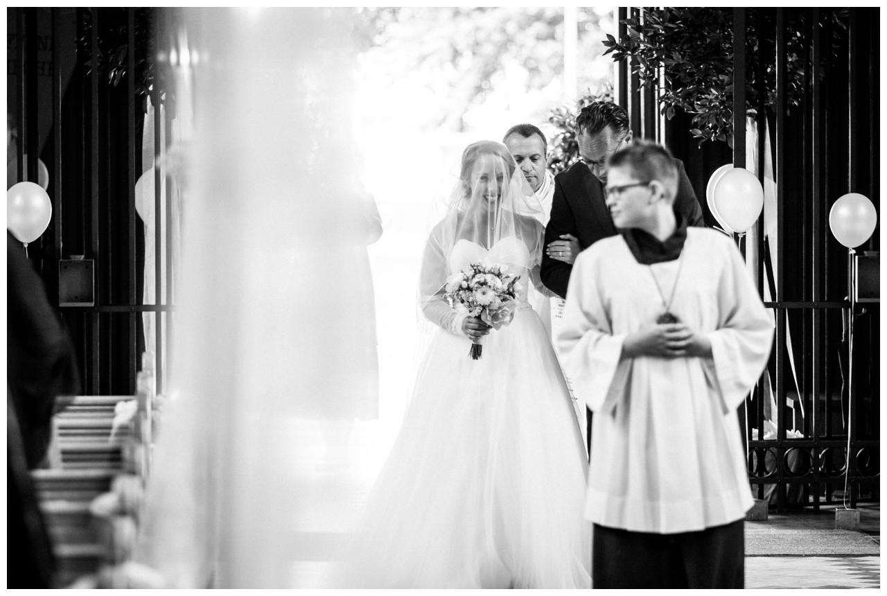 Die Braut schreitet am Arm des Brautvaters in die Kirche in Mönchengladbach