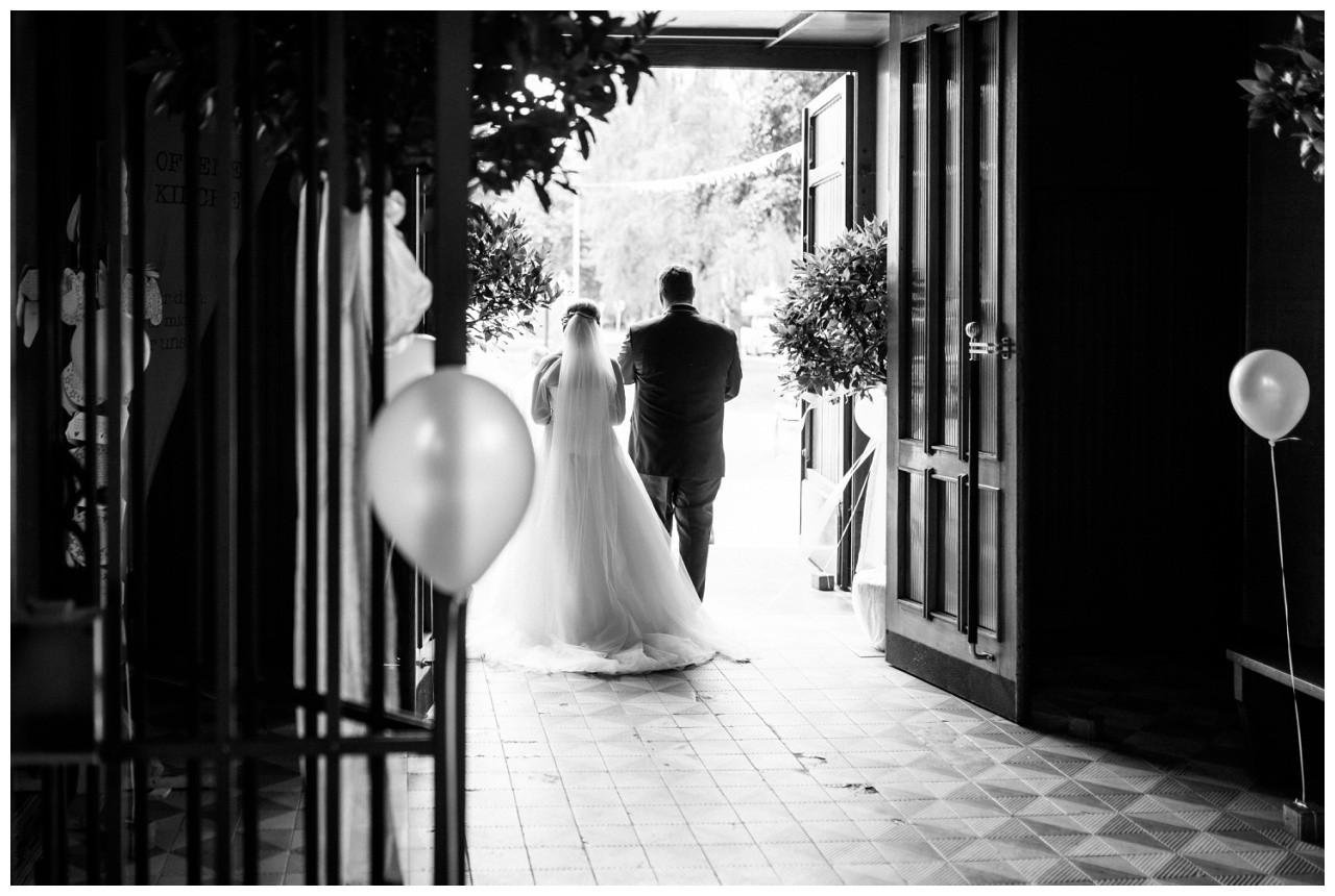 Braut und Bräutigam sind von hinten zu sehen bei der Hochzeit in Mönchengladbach