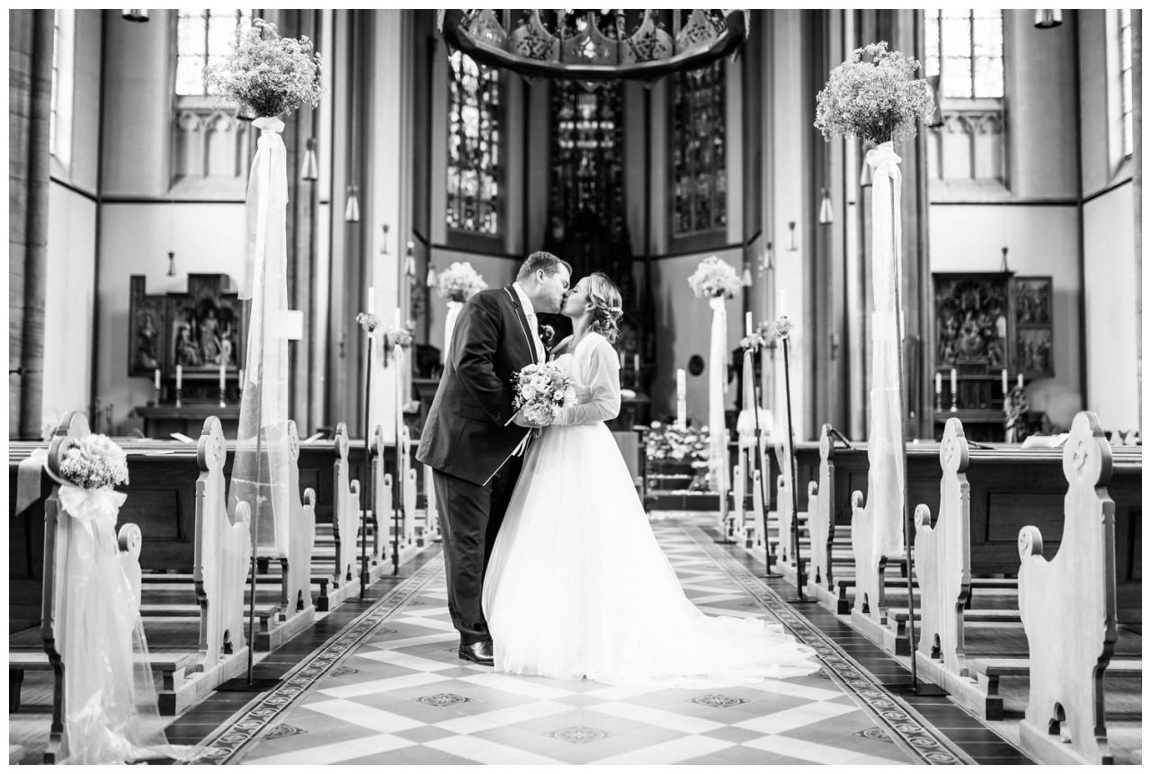 Braut und Bräutigam küssen sich in der Kirche in Mönchengladbach