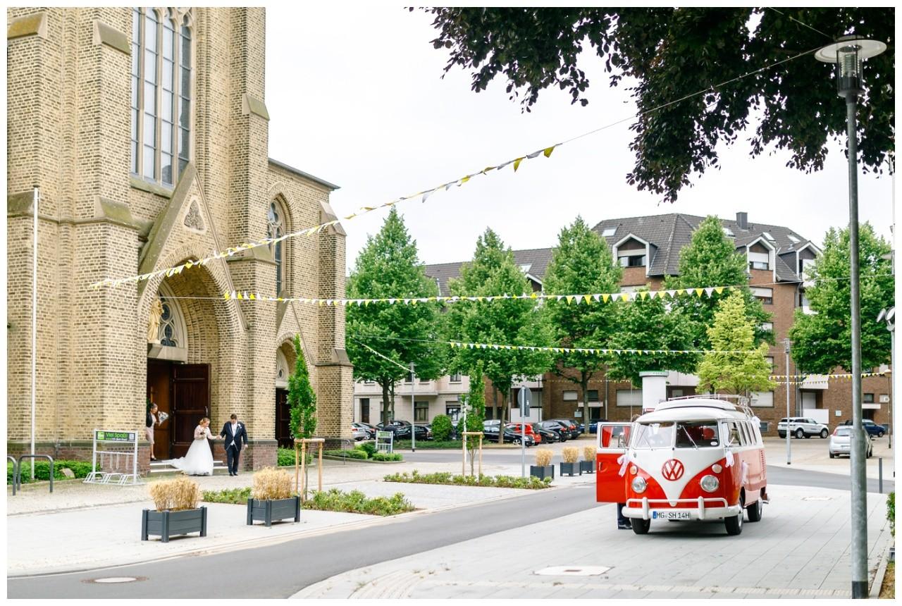 Der alte VW Bulli als Brautauto steht vor der Kirche
