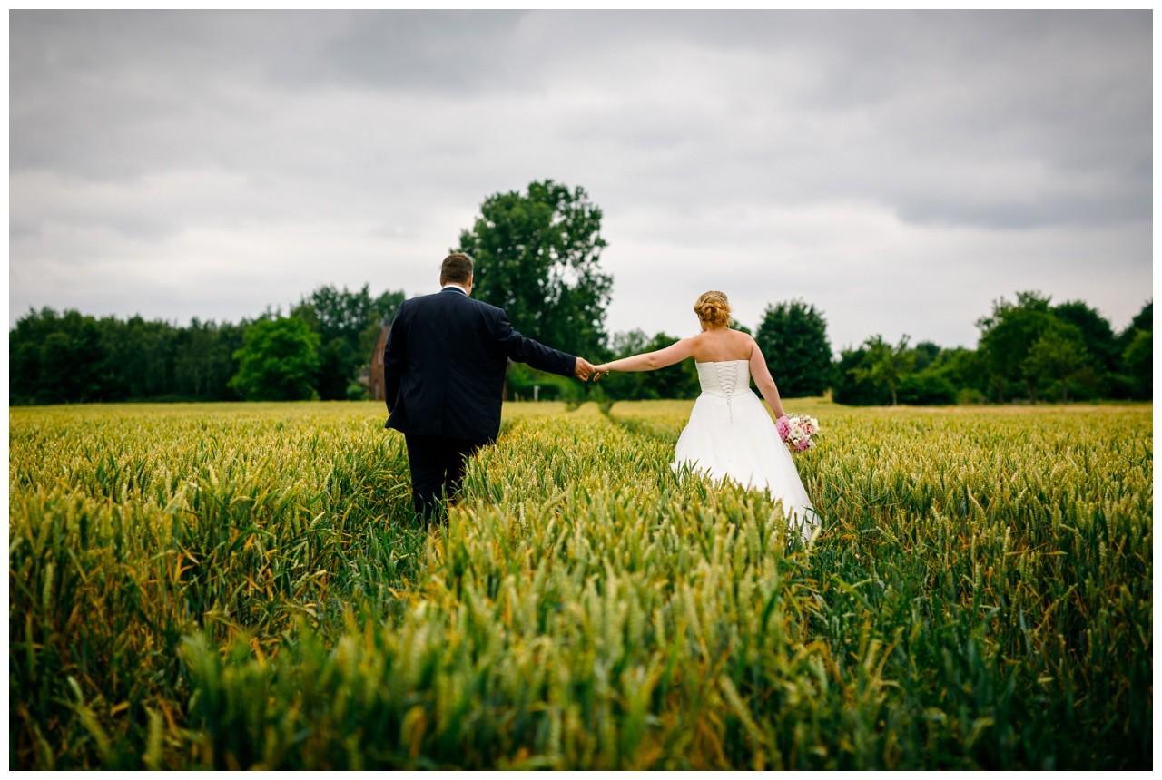 Braut ubd Bräutigam gehen Hand in Hand den Feldweg entlang beim Paarshooting zur Hochzeit in der Elfrather Mühle in Krefeld