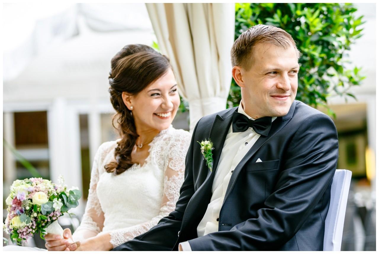 Braut und Bräutigam sitzen vor dem Altar und schauen zu den Gästen hinter sich