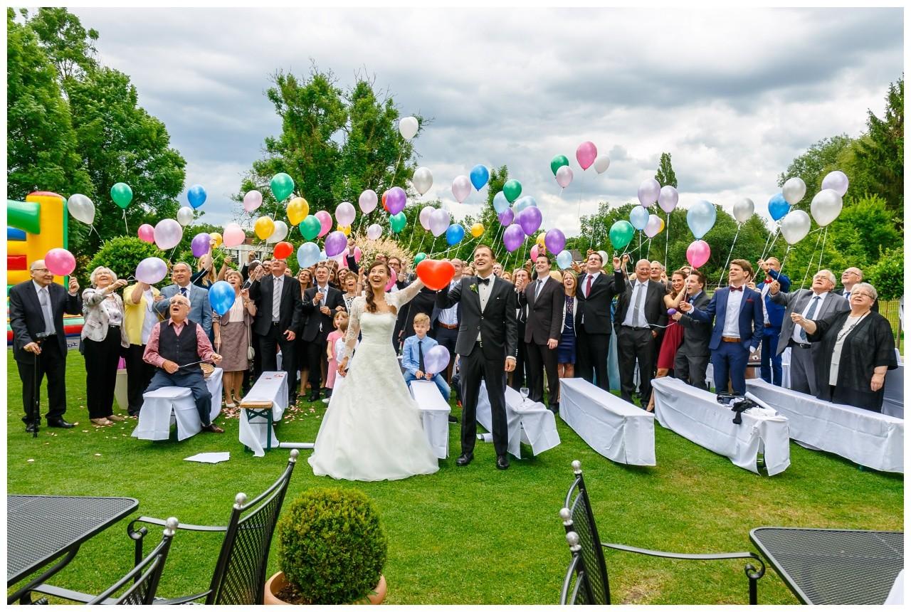 Die Hochzeitsgäste und das Brautpaar lassen bunte Luftballons steigen.