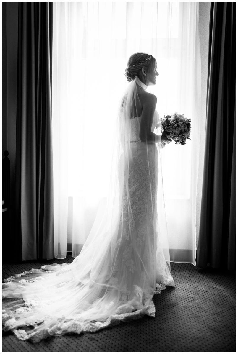 Die Braut in ihrem Mermaid Brautkleid steht vor den großen Fenster in der Engelsburg in Recklinghausen