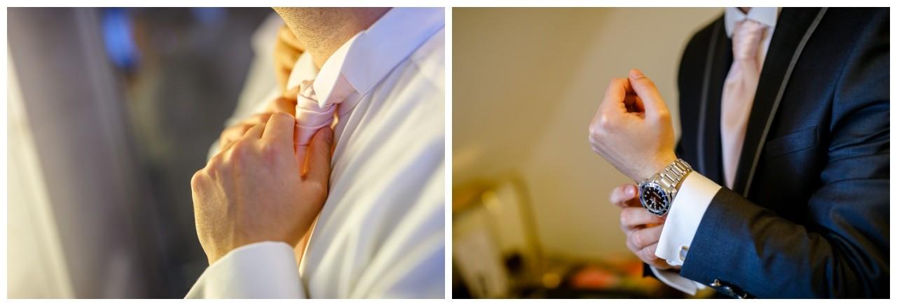 Der Bräutigam zieht sich seinen Plastron an vor der Hochzeit in Recklinghausen