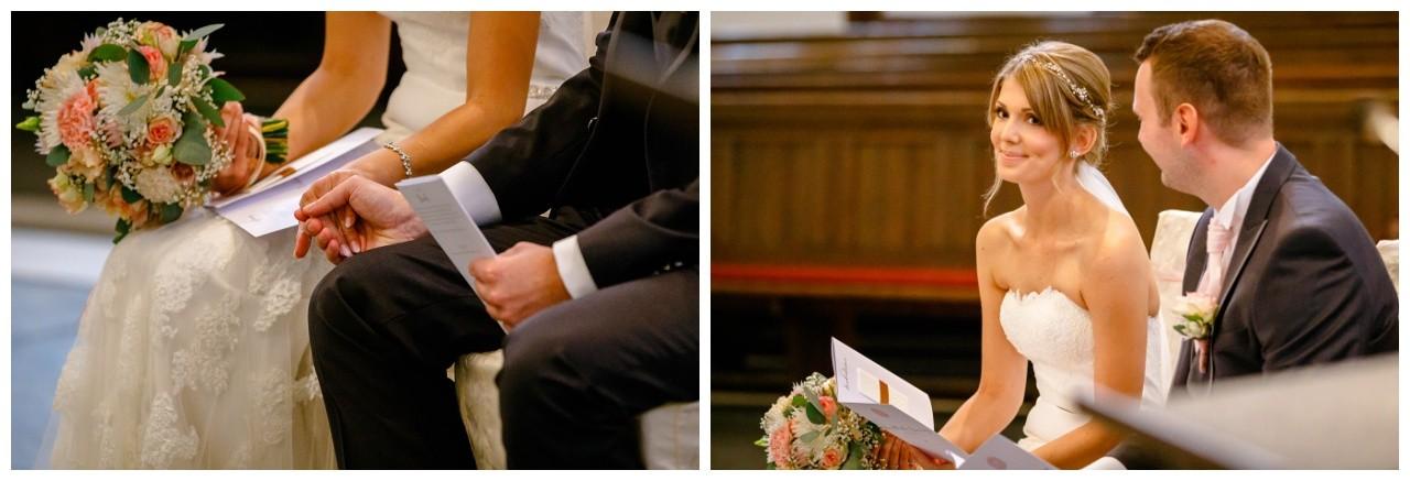 Das Brautpaar sitzt am Altar und hält Händchen bei der kirchlichen Trauung