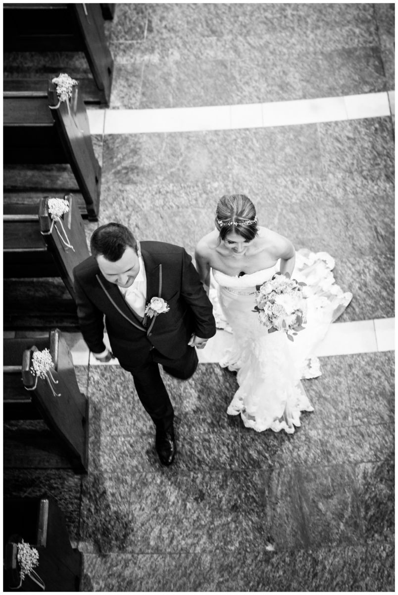 Das Brautpaar geht gemeinsam aus der Kirche, fotografiert von oben vom Hochzeitsfotograf Recklinghausen