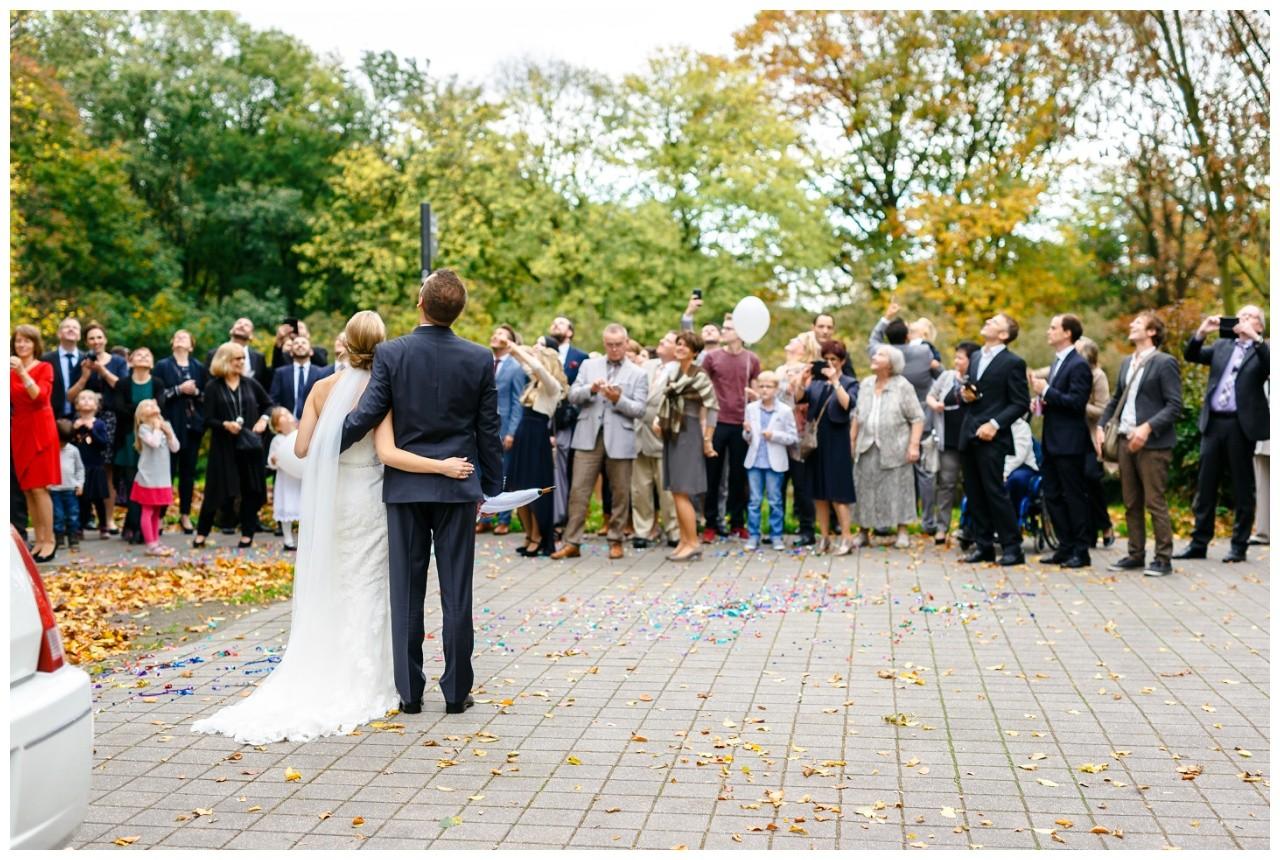 Die Gäste bei der Hochzeit begrüßen das Brautpaar