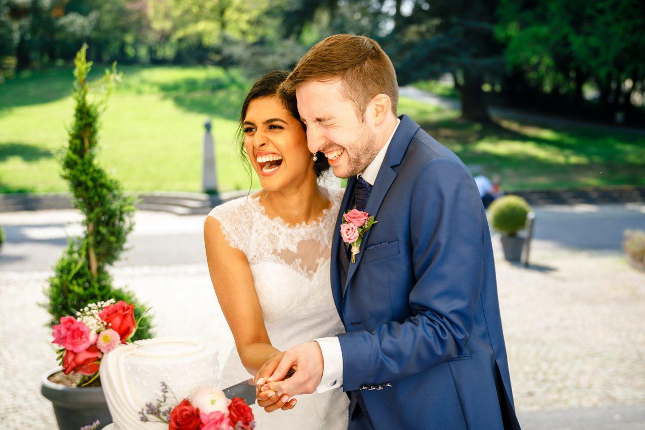 Tortenanschnitt, das Brautpaar schneidet die Hochzeitstorte an und lacht bei der Hochzeit in Bonn