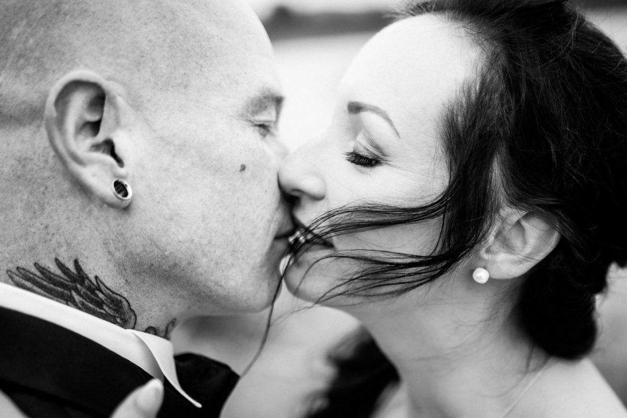 Hochzeitsbild in schwarz weiß, das Brautpaar küsst sich im Wind bei der Hochzeit in Sundern