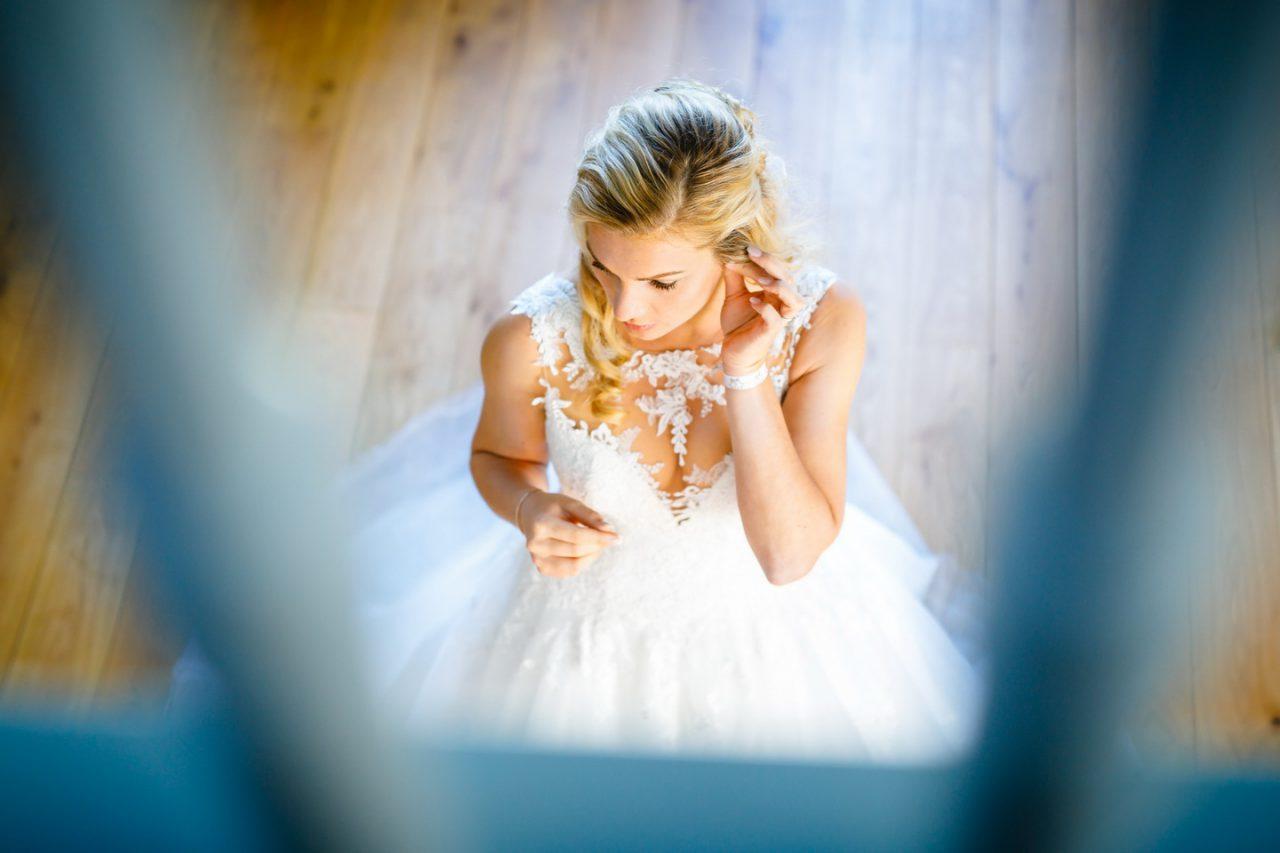 Getting Ready die Braut steckt sich ihre Ohrringe ein