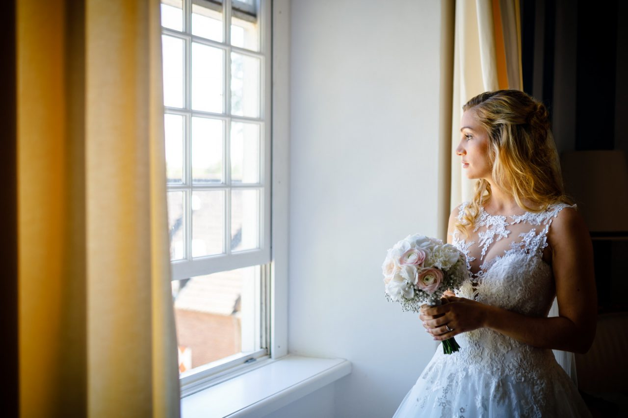 Die Braut sieht aus dem Fenster bei der Hochzeit auf Schloss Hertefeld in Weeze