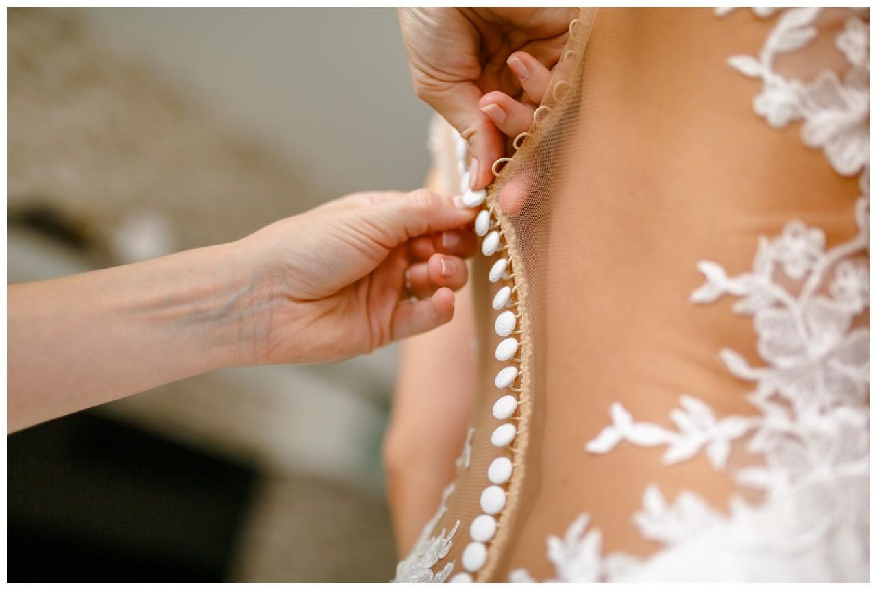 Die Trauzeugin schließt die Knöpfe des Brautkleids bei der Hochzeit in Köln