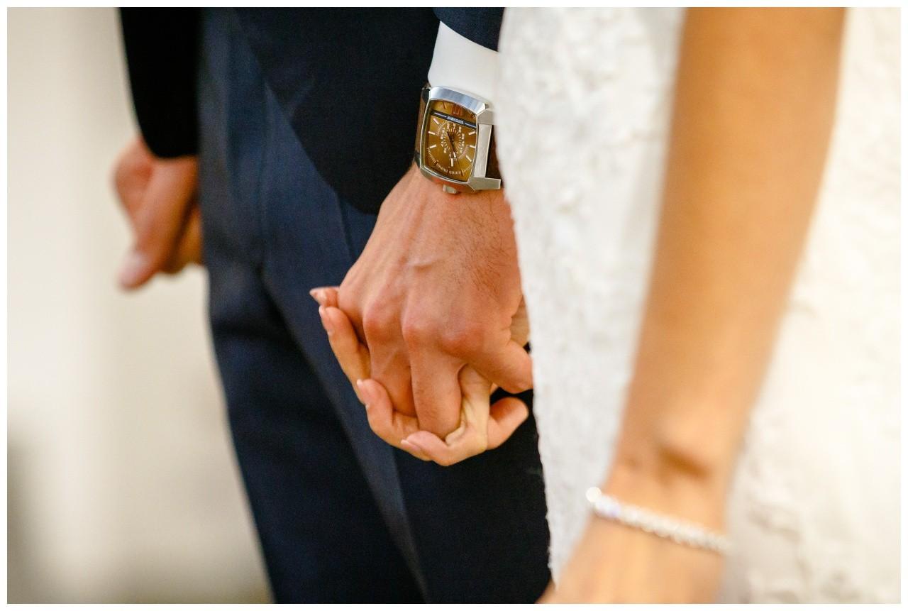 Braut und Bräutigam halten sich bei der Hand