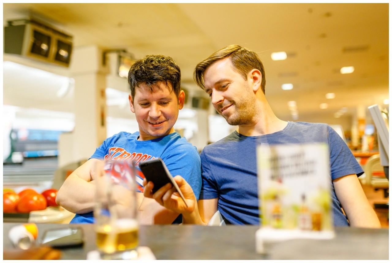 Bräutigam und Trauzeuge checken auf der Bowlingbahn in Wuppertal die Handys