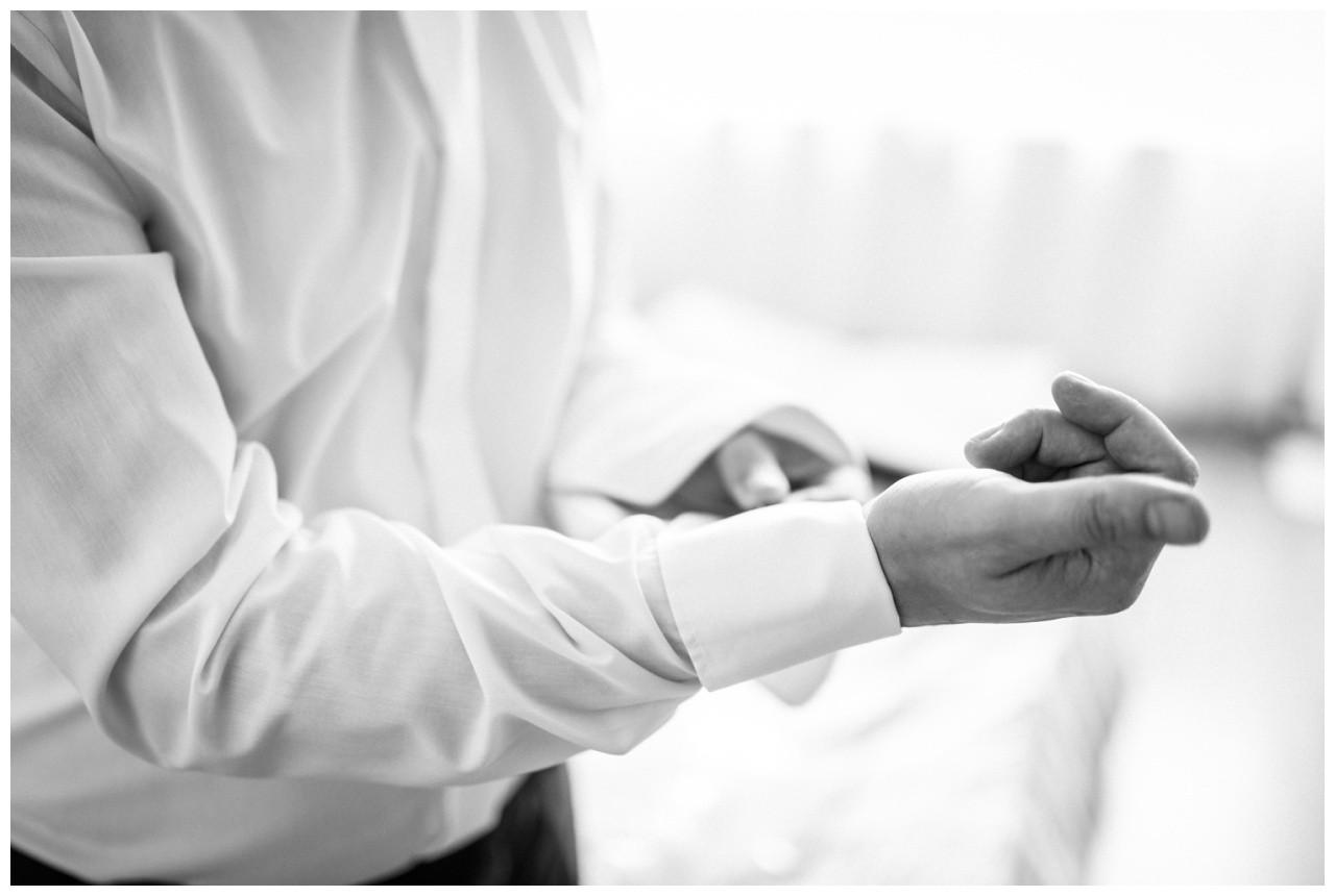 Der Bräutigam macht seine Manschettenknöpfe zu vor der Hochzeit in Wuppertal