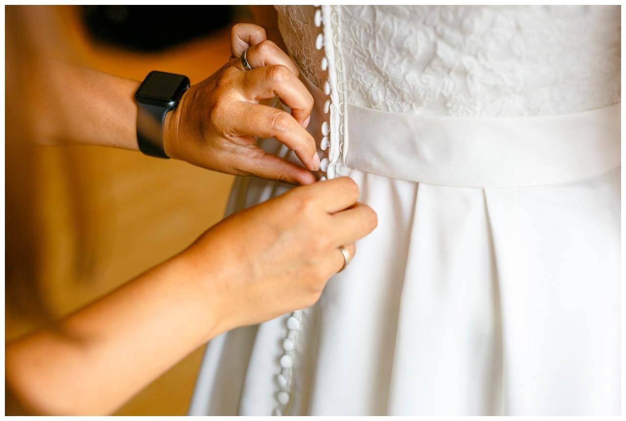 Das Brautkleid wird zugeknöpft vor der Hochzeit im Elisenturm in Wuppertal