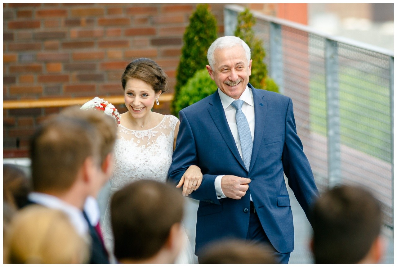 Die Braut am Arm des Brautvaters geht den Mittelgang entlang bei der Freien Trauung