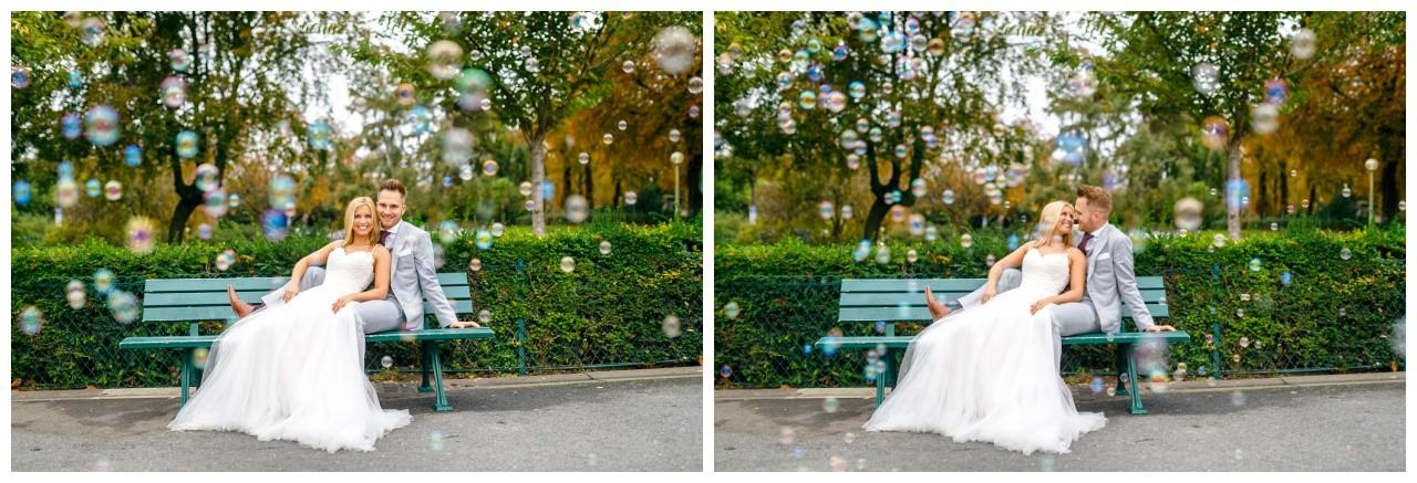 Hochzeitsfotos in Paris das Brautpaar sitzt mit Seifenblasen auf einer Bank