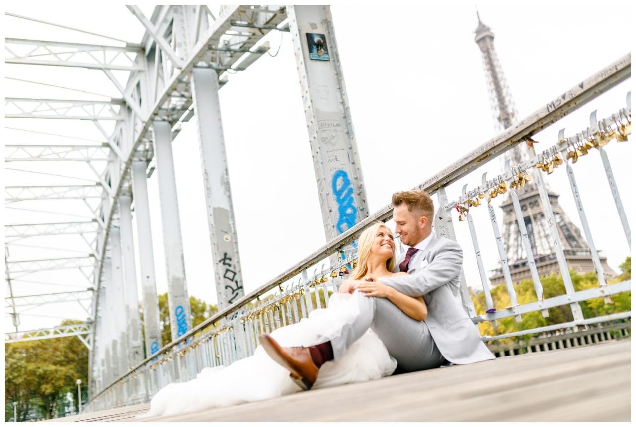 After Wedding Shooting in Paris, Braut und bräutigam sitzen auf einer Brücke vor dem Eiffelturm