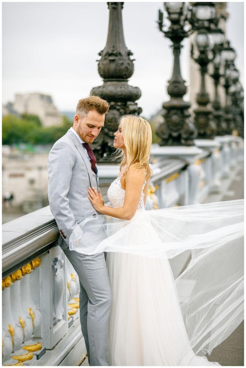 After Weding Shooting in Paris, das Brautpaar steht auf einer Brücke
