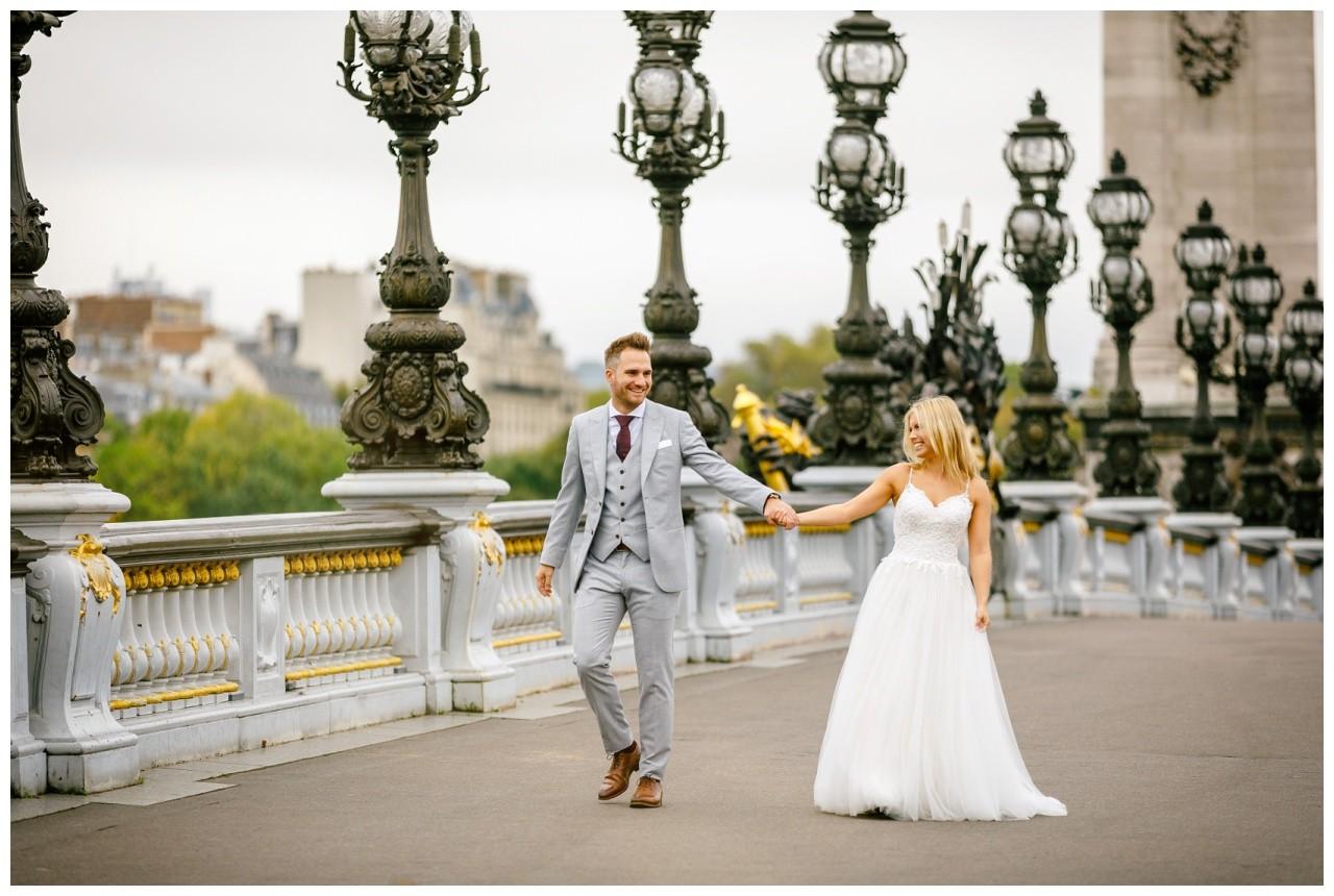 After Wedding Shooting in Paris das Brautpaar läuft eine Brücke entlang