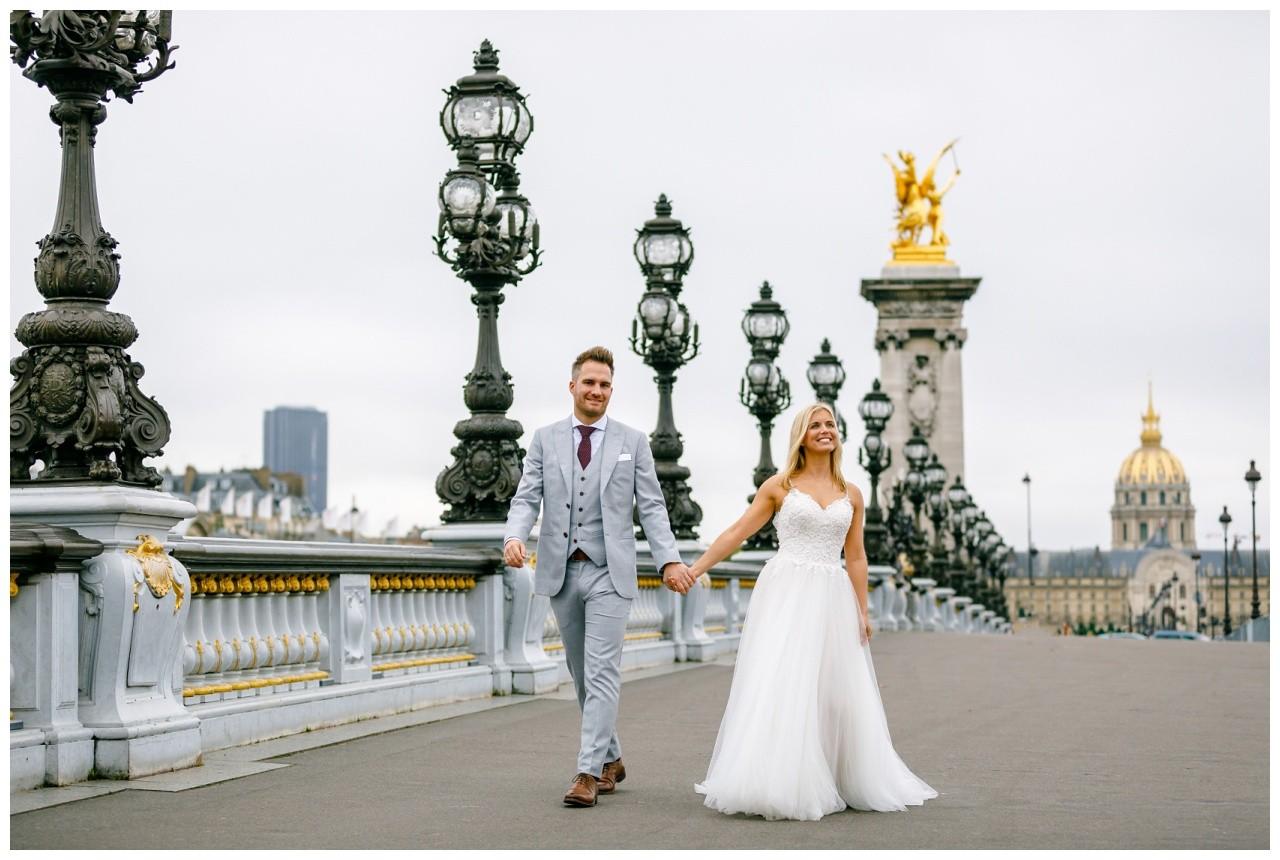 Hochzeitsfotos in Paris das Brautpaar schlendert eine Brücke entlang