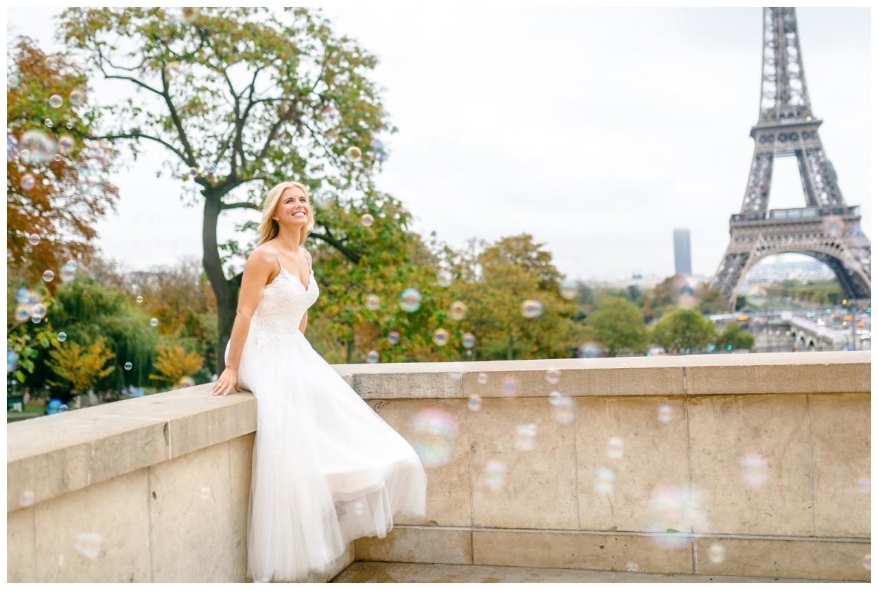 Elopement in Paris, die Braut sitzt vor dem Eiffelturm und schaut den Seifenblasen hinterher.