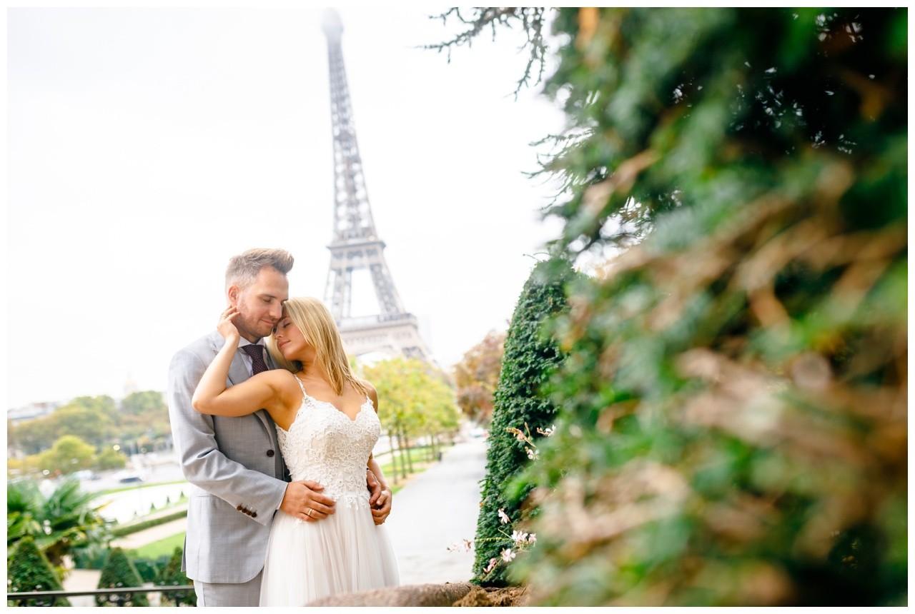 Destinationwedding in Paris, Hochzeitsfotos vor dem Eiffelturm, das Brautpaar schmust verliebt.