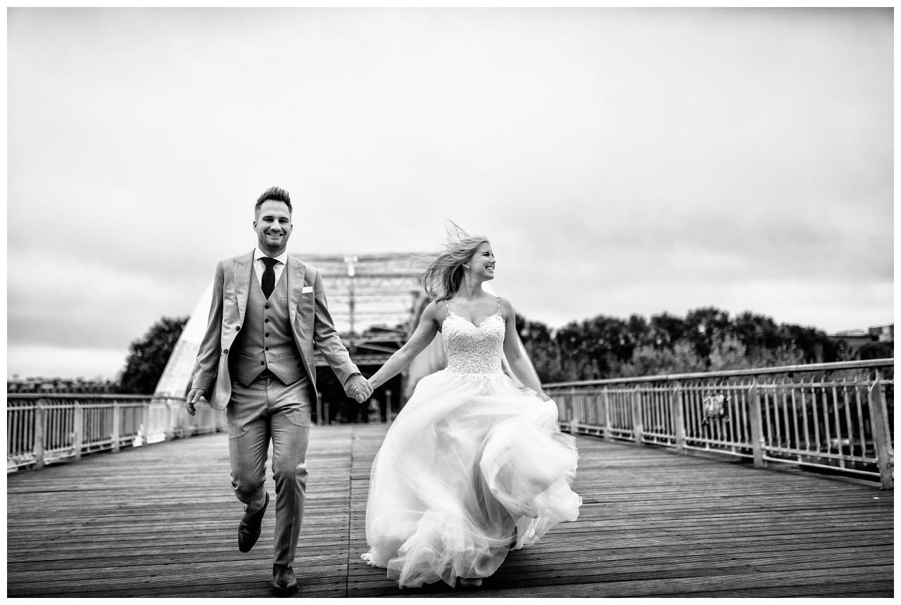 After Wedding Shooting in Paris, das Brautpaar rennt über eine Brücke.