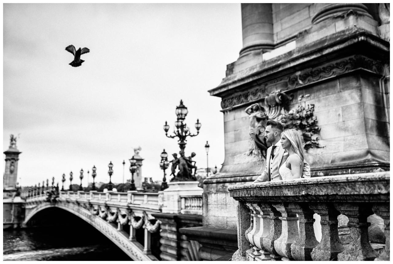 Hochzeit in Paris, das Brautpaar steht bei seinem After Wedding Shooting in Paris auf der Brücke.