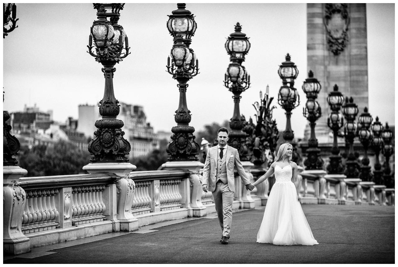 After Wedding Shooting in Paris, das Brautpaar läuft über eine Brücke und der Hochzeitsfotograf Paris begleitet sie dabei und macht Hochzeitsfotos.