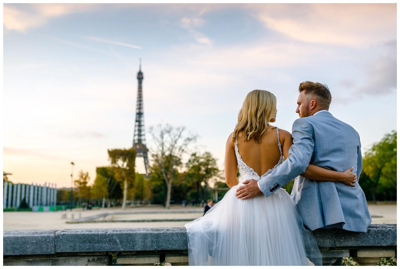 Das Brautpaar sitzt in Paris auf einer Bank und sieht den Eiffelturm beim After Weding Shooting.