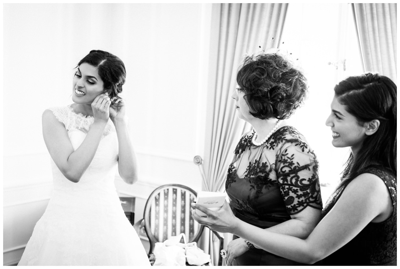 Die Braut steckt sich ihre Ohrringe zur Hochzeit in der Redoute in Bonn ein.