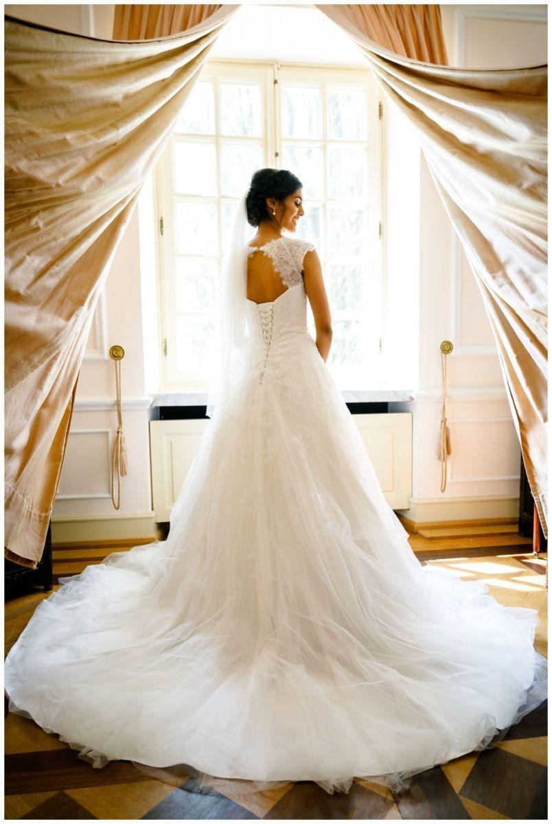 Die Braut steht am Fenster und ihr Brautkleid ist zu sehen.