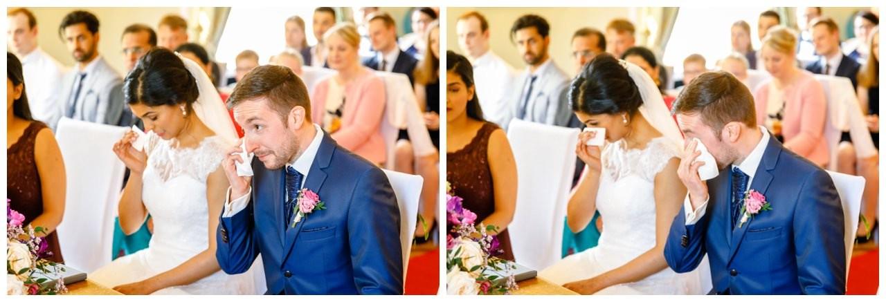 Braut und Bräutigam wischen sich die Augen trocken bei der Hochzeit im La Redoute in Bonn